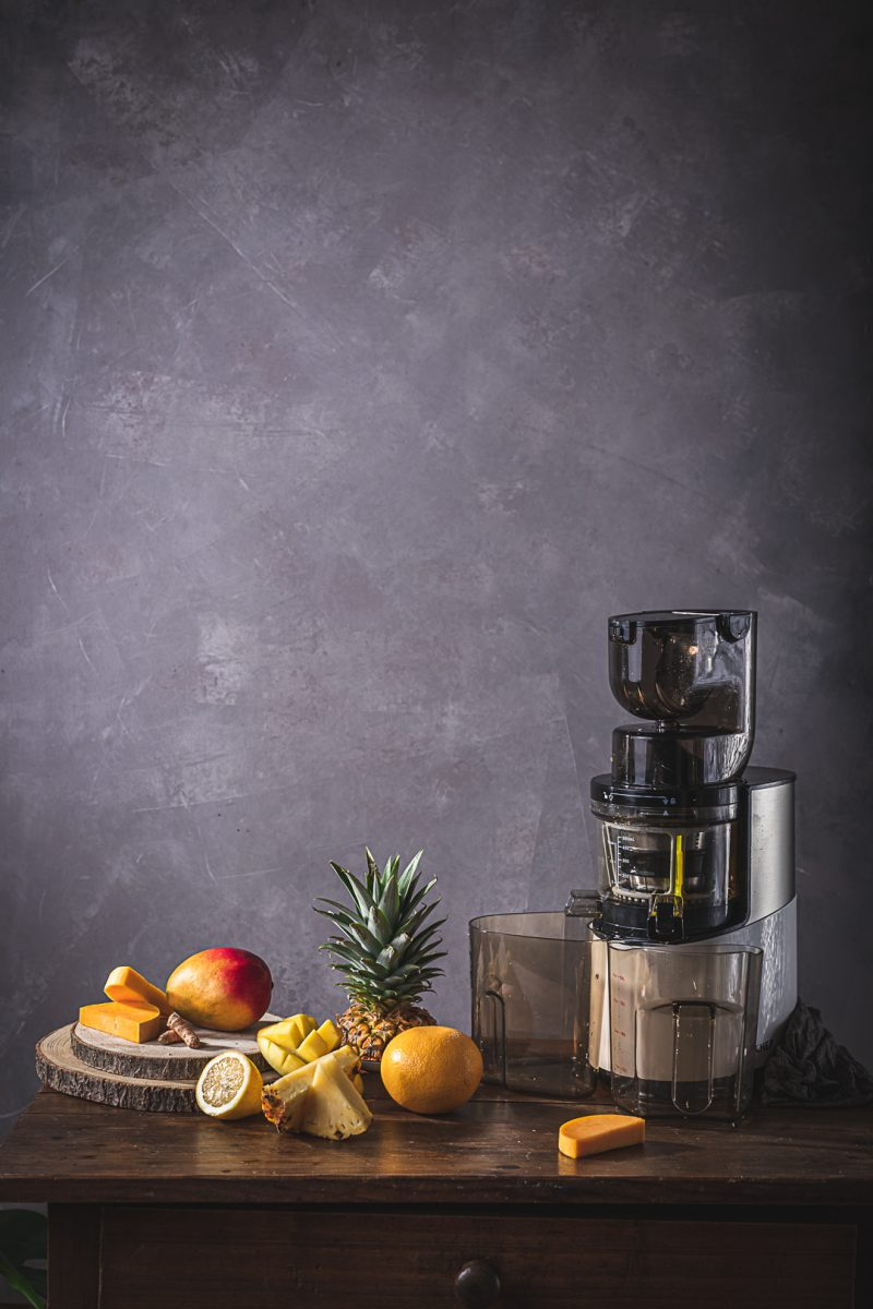 juicer and fresh fruit in yellow tones
