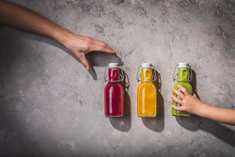 small bottles with yellow, pink and green juice